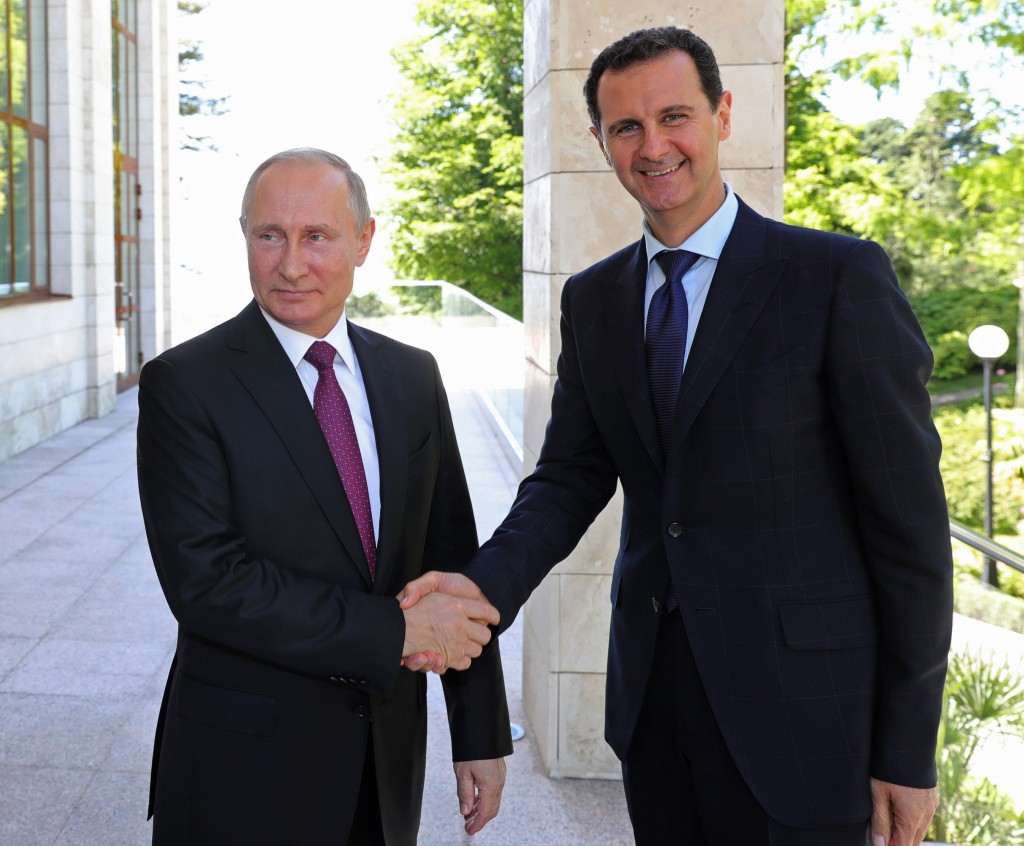 FILE - In this May 17, 2018 file photo, Russian President Vladimir Putin, left, shakes hands with Syrian President Bashar al-Assad during their meetin
