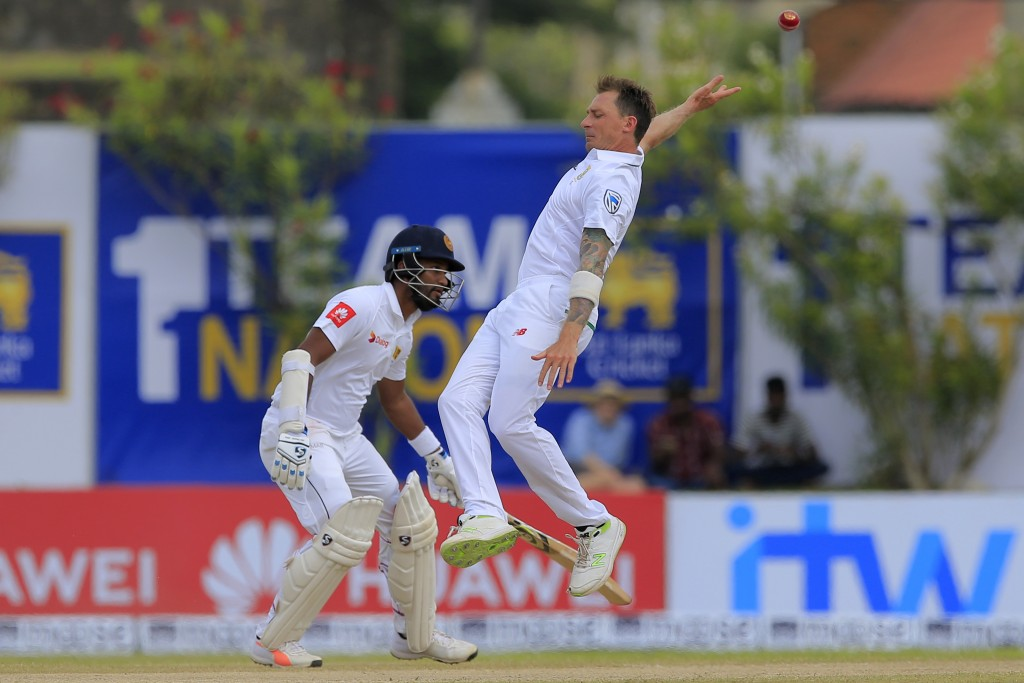 South Africa's Dale Steyn reaches to field a ball as Sri Lanka's Dimuth Karunaratne watches during the second day of their first test cricket match in