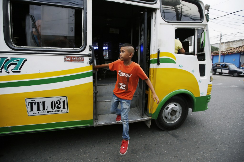 In this June 28, 2018 photo, young Venezuelan migrant Jhon Jader Duno exits a bus after panhandling commuters in Cucuta, Colombia. Duno said he's tryi