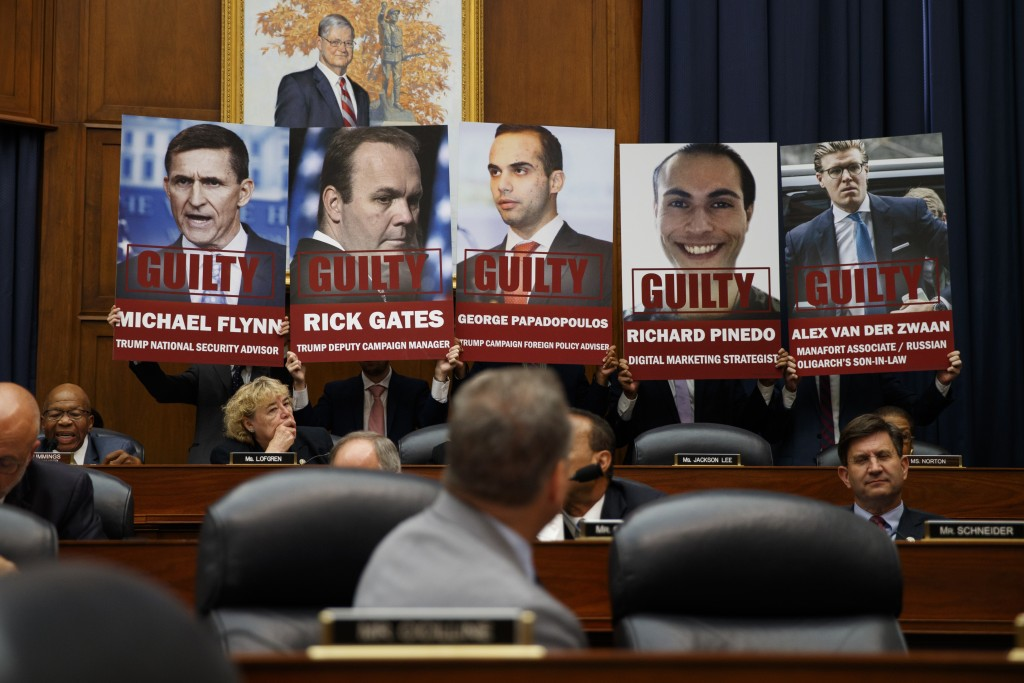"""Staff members hold up posters in a House Committees on the Judiciary and Oversight and Government Reform hearing on """"Oversight of FBI and DOJ Actions"""