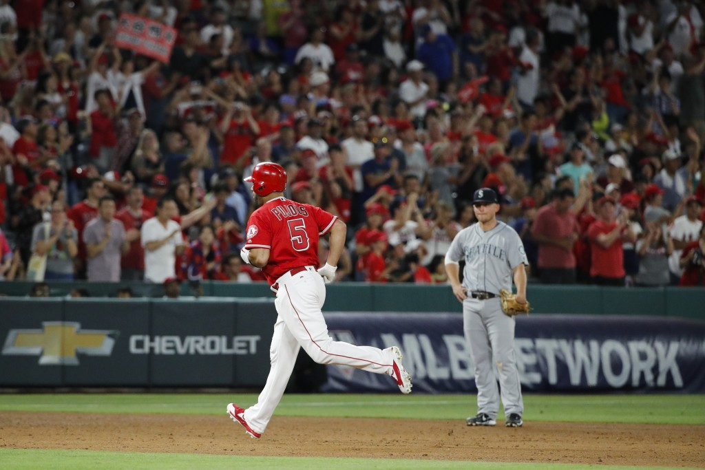 Los Angeles Angels' Albert Pujols rounds the bases past Seattle Mariners' Kyle Seager after hitting a home run, his second homer of the night, during