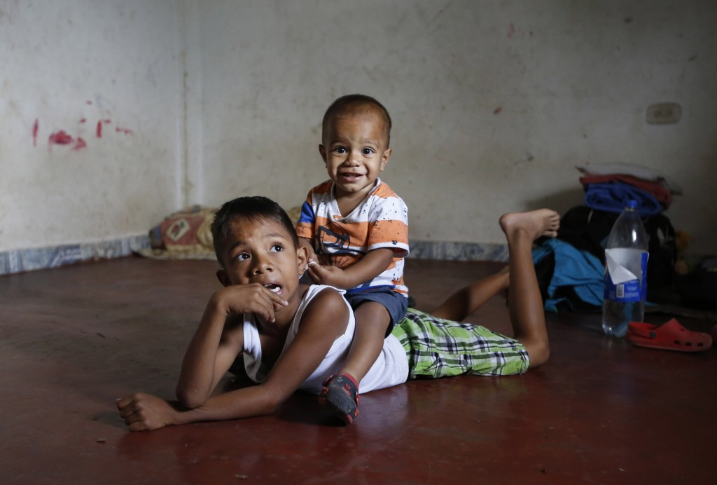 In this June 27, 2018 photo, Venezuelan migrant children play on the floor of the unfurnished home their parents are renting and sharing for the last