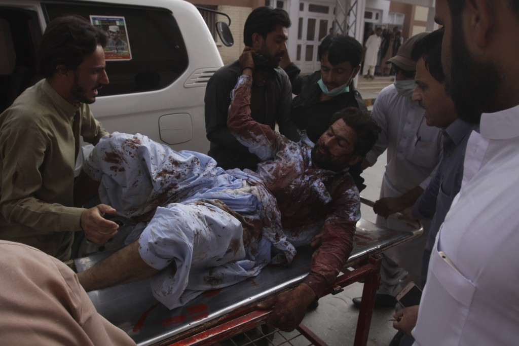 People rush an injured person to a hospital in Quetta, Pakistan, Friday, July 13, 2018. Underscoring the security threat, two bombs exploded Friday ki