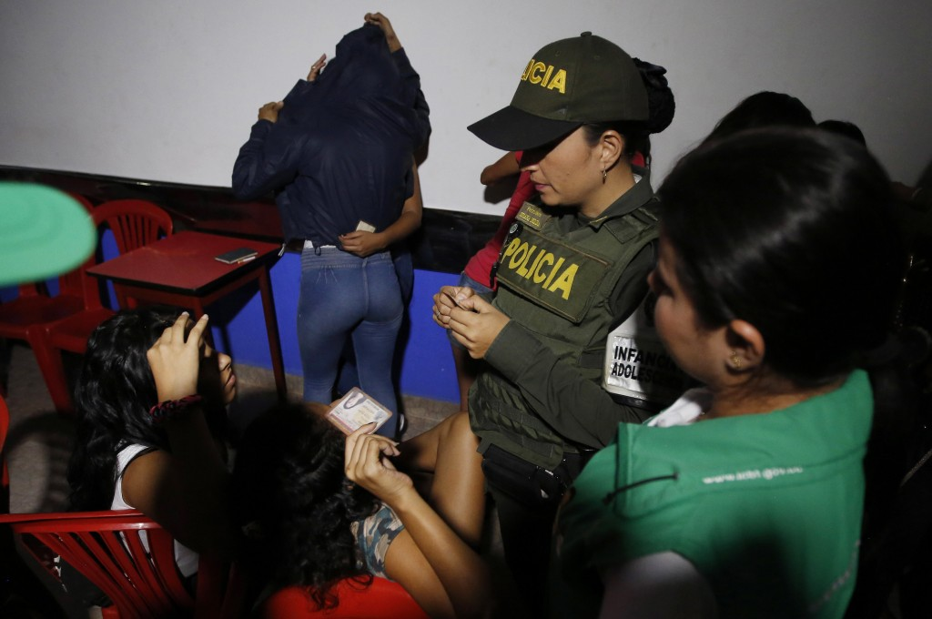 In this June 26, 2018 photo, police look at the identification cards of Venezuelan girls to check their ages as they search for minors at a bar known