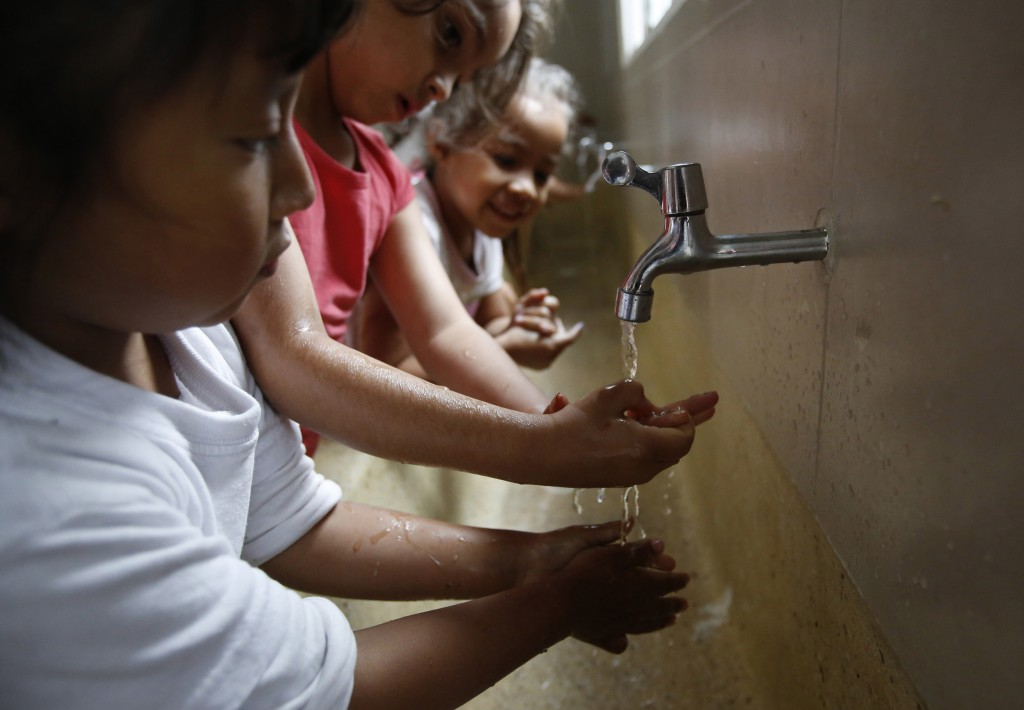 In this July 4, 2018 photo, children, some of them Venezuelan migrants, wash their hands before lunch at the child development center Social Foundatio