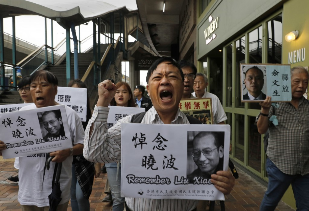 Protesters hold placards with picture of late Chinese Nobel Peace laureate Liu Xiaobo during a protest in Hong Kong, Friday, July 13, 2018, to mark th