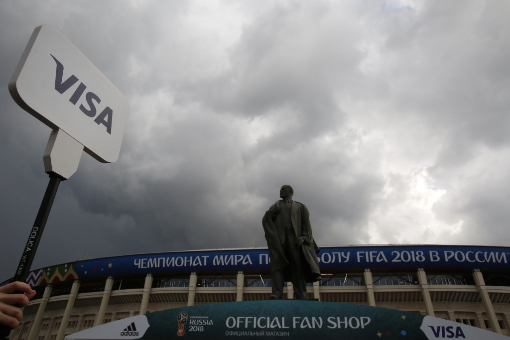 In this July 11, 2018 photo, a man holds up a Visa sign in front of a statue of Lenin, as fans arrive for the semifinal match between Croatia and Engl