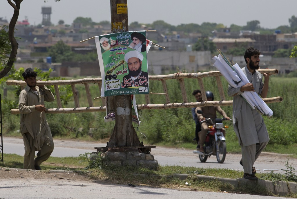 In this July 5, 2018 photo, workers from the Pakistani radical political party, Tehreek-i-Labbaik Ya Rasool Allah, hang election posters for their can