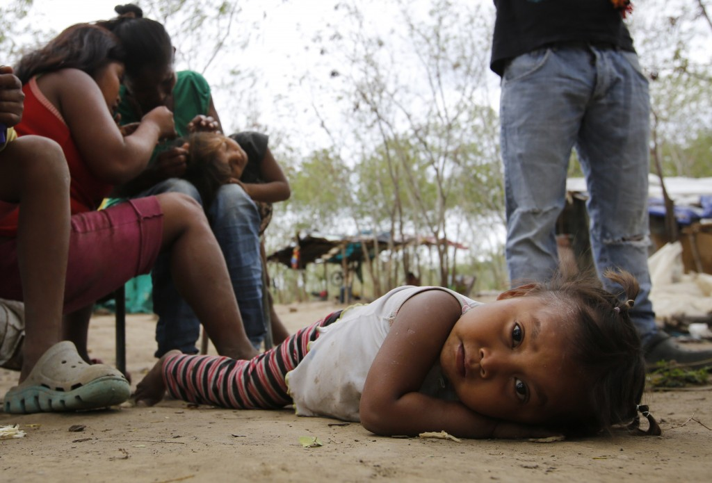 In this June 26, 2018 photo, a Venezuelan indigenous Yupka girl plays on the ground while another gets lice picked from her head at a camp set up in C