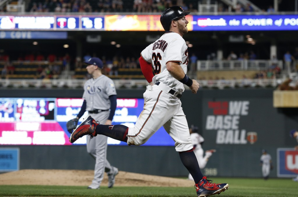 Minnesota Twins' Robbie Grossman jogs home on a double by Jorge Polanco off Tampa Bay Rays pitcher Blake Snell, left, during the third inning of a bas