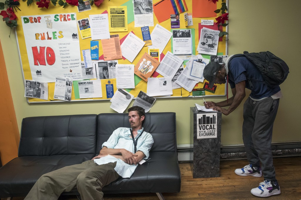 In this Tuesday, July 3, 2018, photo, peer educator Chris Marshal, left, takes a nap as a member signs in before using the bathroom at the VOCAL-NY he