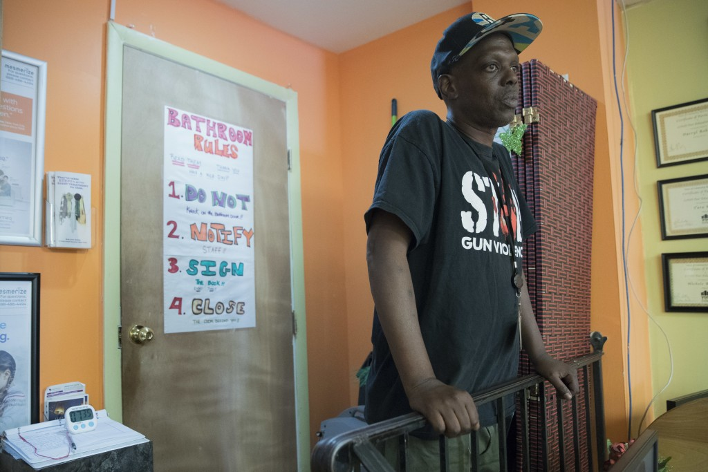 In this Tuesday, June 19, 2018, photo, peer educator Jeffery Foster stands outside as a member uses the bathroom at VOCAL-NY headquarters in the Brook