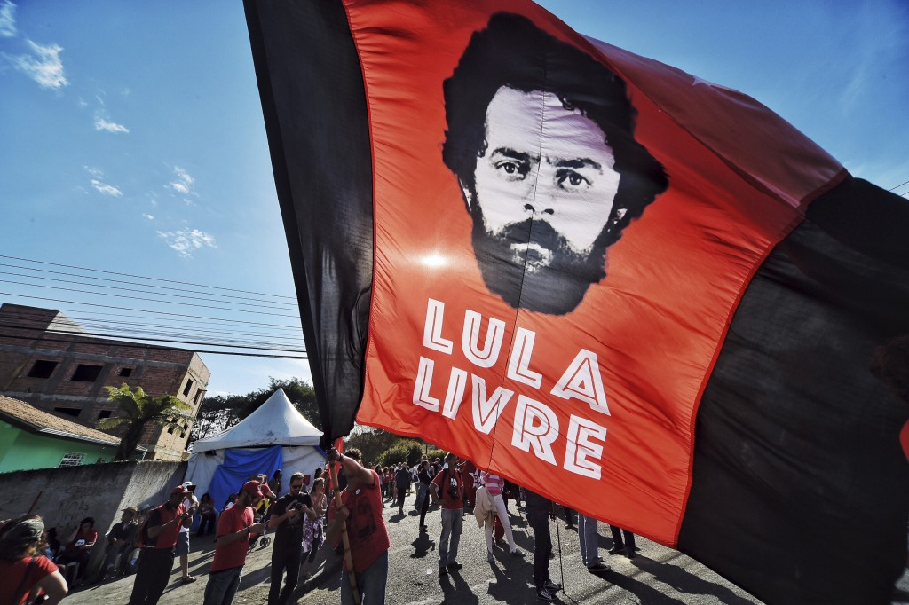 "In this July 8, 2018 photo, a supporter of ex-President Luiz Inacio Lula da Silva holds a flag that reads in Portuguese: ""Free Lula,"" in front of the"
