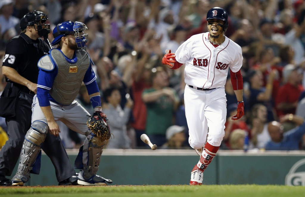 Boston Red Sox's Mookie Betts reacts in front of Toronto Blue Jays' Russell Martin, left, after hitting a grand slam during the fourth inning of a bas