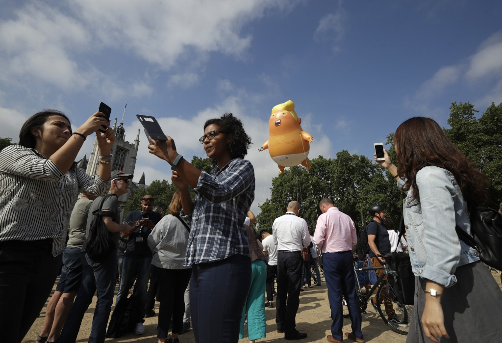 People take photos of a six-meter high cartoon baby blimp of U.S. President Donald Trump is flown as a protest against his visit, in Parliament Square