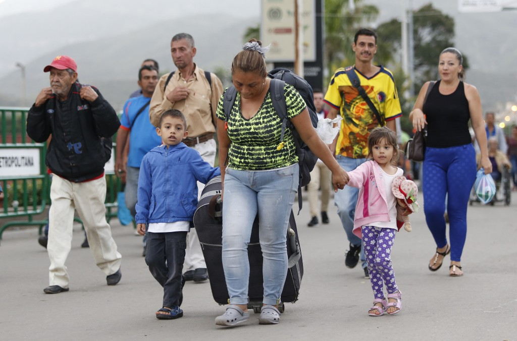 In this June 28, 2018 photo, Venezuelan migrant mother Yelitza Fuenmayor crosses the Simon Bolivar International Bridge into Colombia with her childre