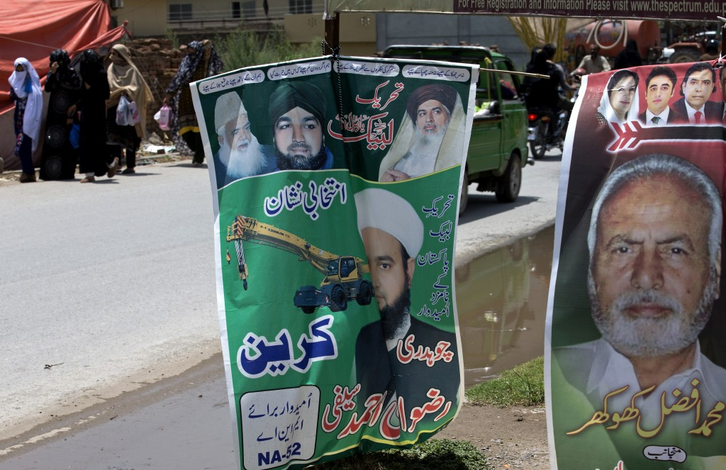 In this July 5, 2018 photo, a poster for the Pakistani radical political party, Tehreek-i-Labbaik Ya Rasool Allah, center, are displayed alongside a b