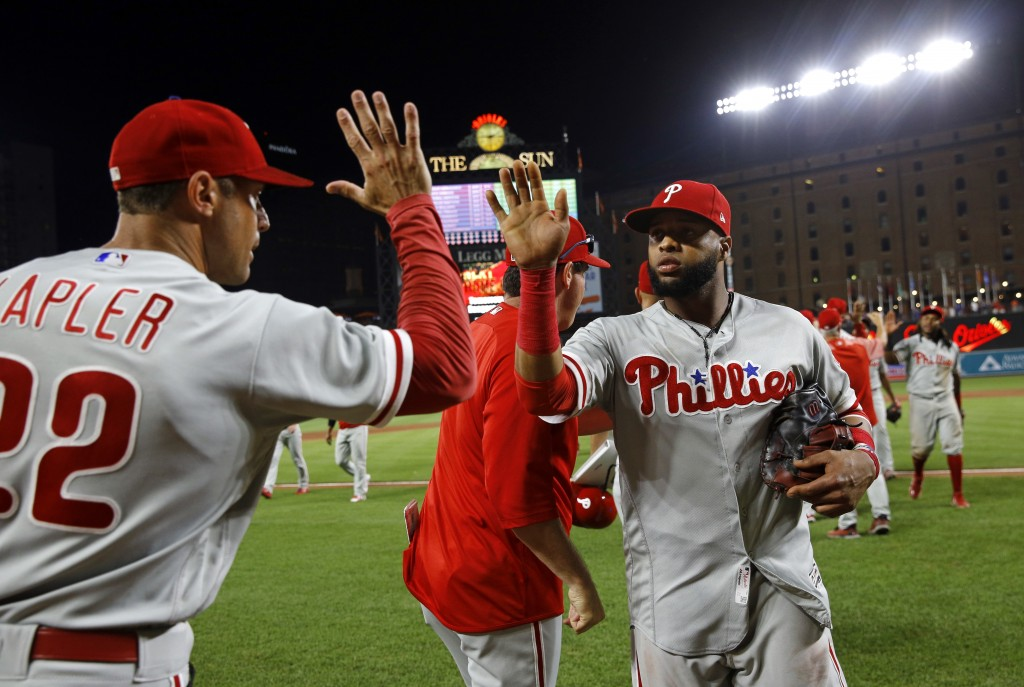 Philadelphia Phillies' Carlos Santana, right, high-fives manager Gabe Kapler after the team's baseball game against the Baltimore Orioles, Thursday, J