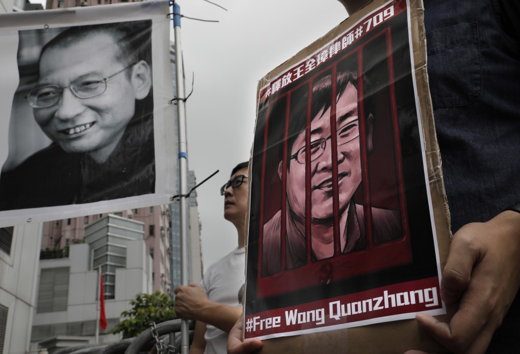 Protesters hold pictures of late Chinese Nobel Peace laureate Liu Xiaobo, left, and imprisoned and a prominent Chinese human rights lawyer Wang Quanzh