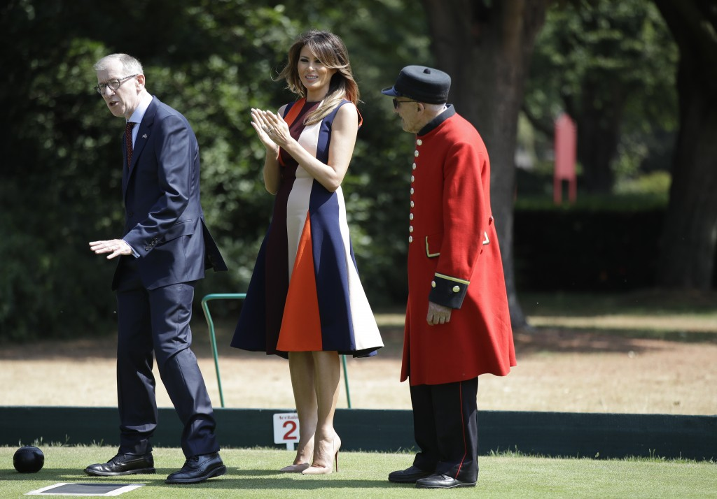U.S. First Lady Melania Trump claps as she plays bowls with Philip May, the husband of British Prime Minister Theresa May during a visit to British mi