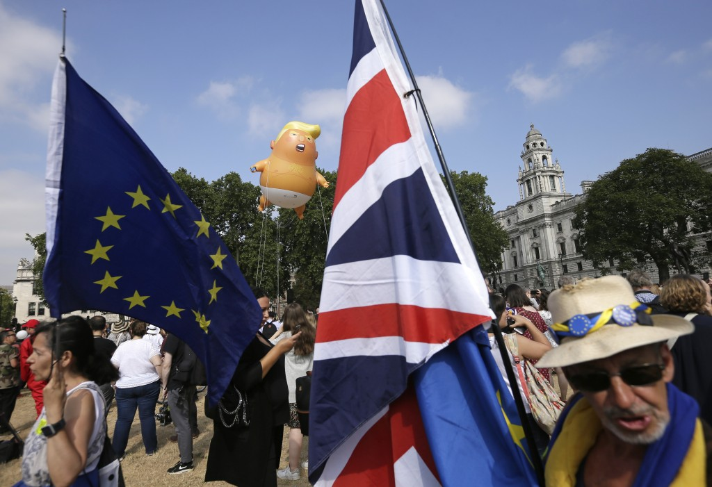 An EU, left, and a British union flag are displayed in front of a six-meter high cartoon baby blimp of U.S. President Donald Trump, as it is flown as