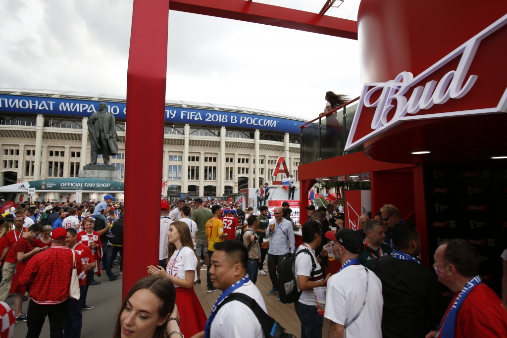 In this July 11, 2018 photo, people walk past a Budweiser pavilion in front of the Luzhniki Stadium as fans arrive for the semifinal match between Cro