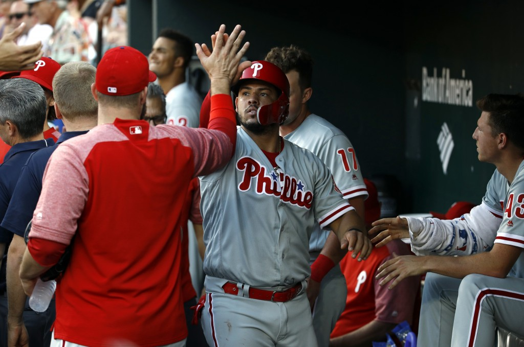 Philadelphia Phillies' Jorge Alfaro high-fives teammates in the dugout after scoring on Carlos Santana's single during the third inning of a baseball