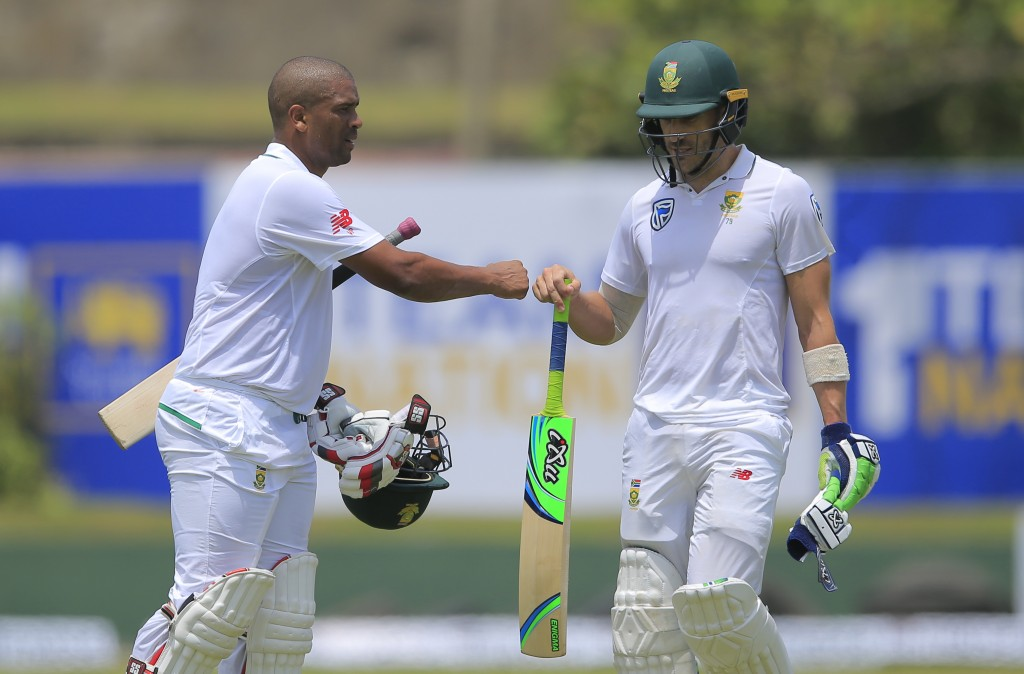 South Africa's captain Fuf du Pleases, right, and teammate Vernon Philander cheer each other as they leave the ground for lunch break during the secon