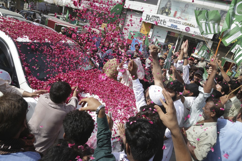 In this Sunday, July 8, 2018 photo, people shower rose petals on a vehicle of Hafiz Saeed, head of the Pakistani religious group Jamaat-ud-Dawa, as he