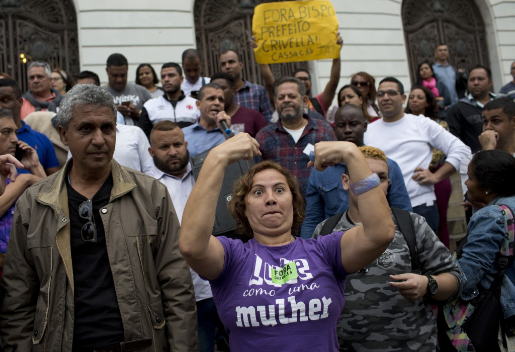In this July 12, 2018 photo, a woman protests against Rio Mayor Marcelo Crivella outside City Hall in Rio de Janeiro, Brazil. Rio's city council is an