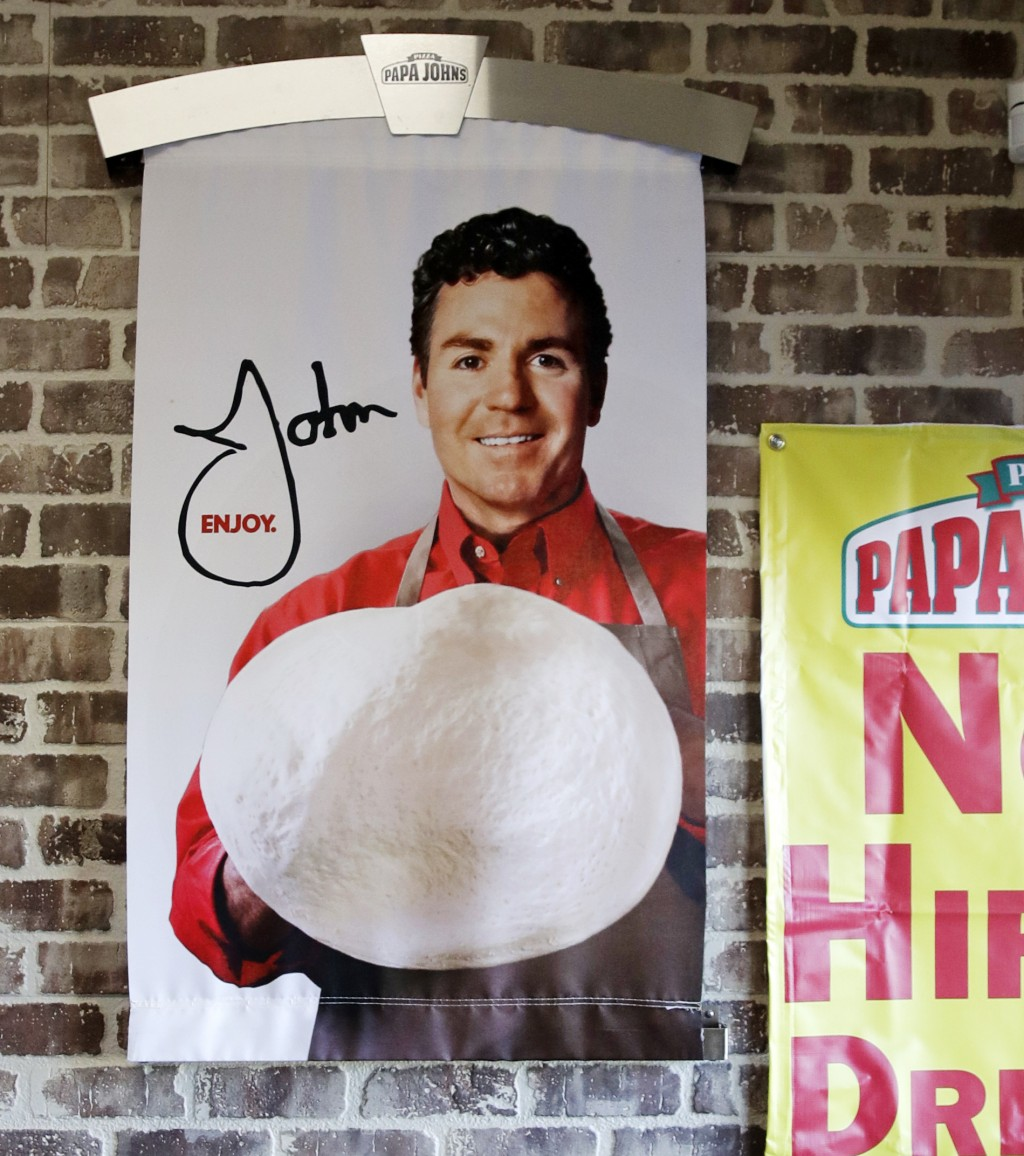 FILE- In this Dec. 21, 2017, file photo shows signs, including one featuring Papa John's founder John Schnatter, at a Papa John's pizza store in Quinc