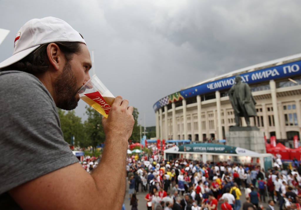 In this July 11, 2018 photo, a man drinks a beer in a Budweiser pavilion in front of Luzhniki Stadium as fans arrive for the semifinal match between C