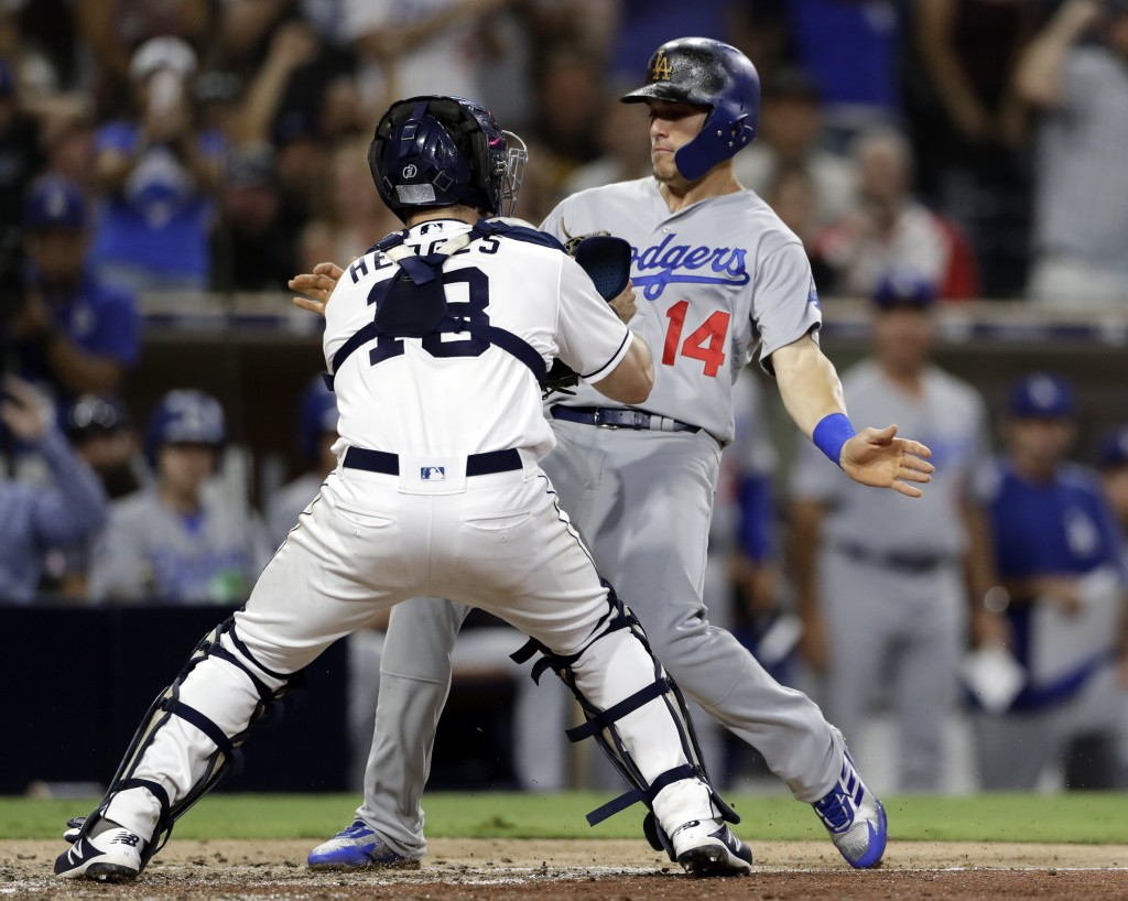 San Diego Padres catcher Austin Hedges, left, tags out Los Angeles Dodgers' Enrique Hernandez (14), who trying to score from second on an RBI single b