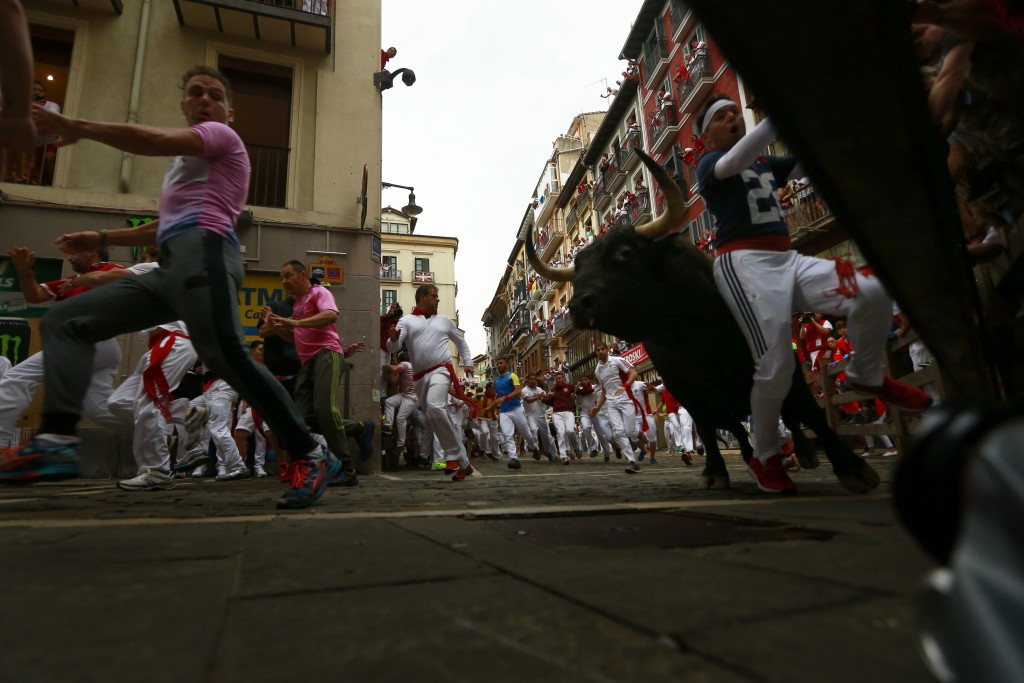 Revellers run next to fighting bulls during the running of the bulls at the San Fermin Festival, in Pamplona, northern Spain, Friday, July 13, 2018. R