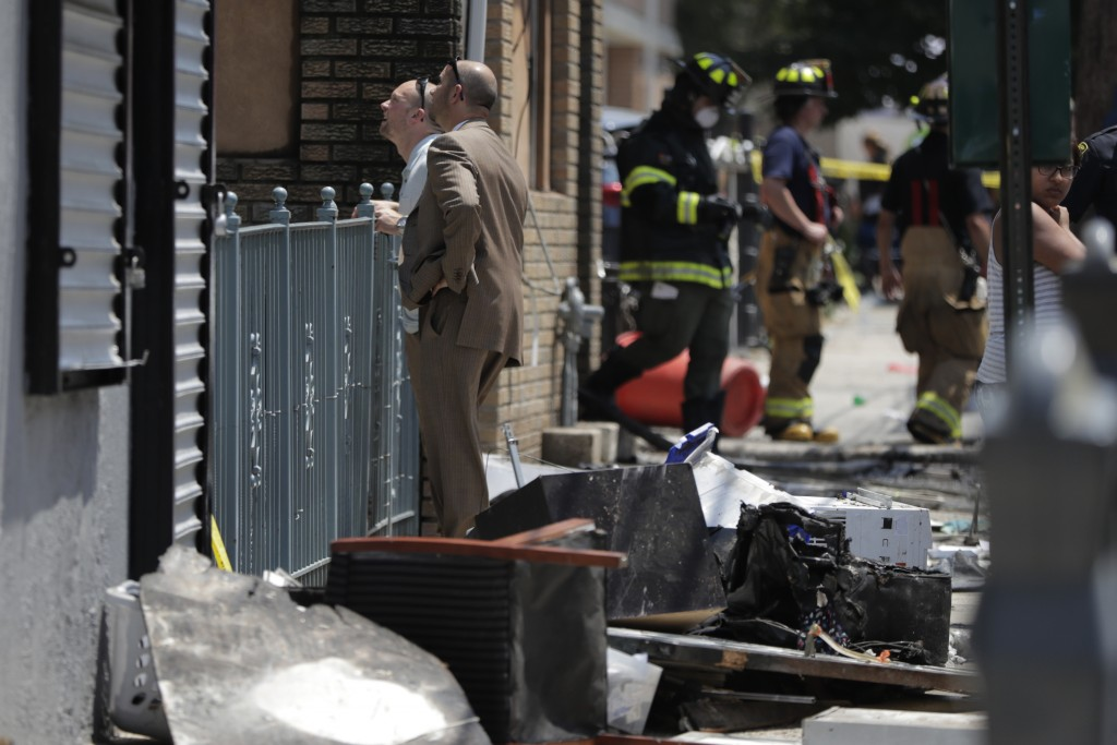 Investigators stand outside of a house where two children were killed in a morning fire, Friday, July 13, 2018, in Union City, N.J.  The fire at the m