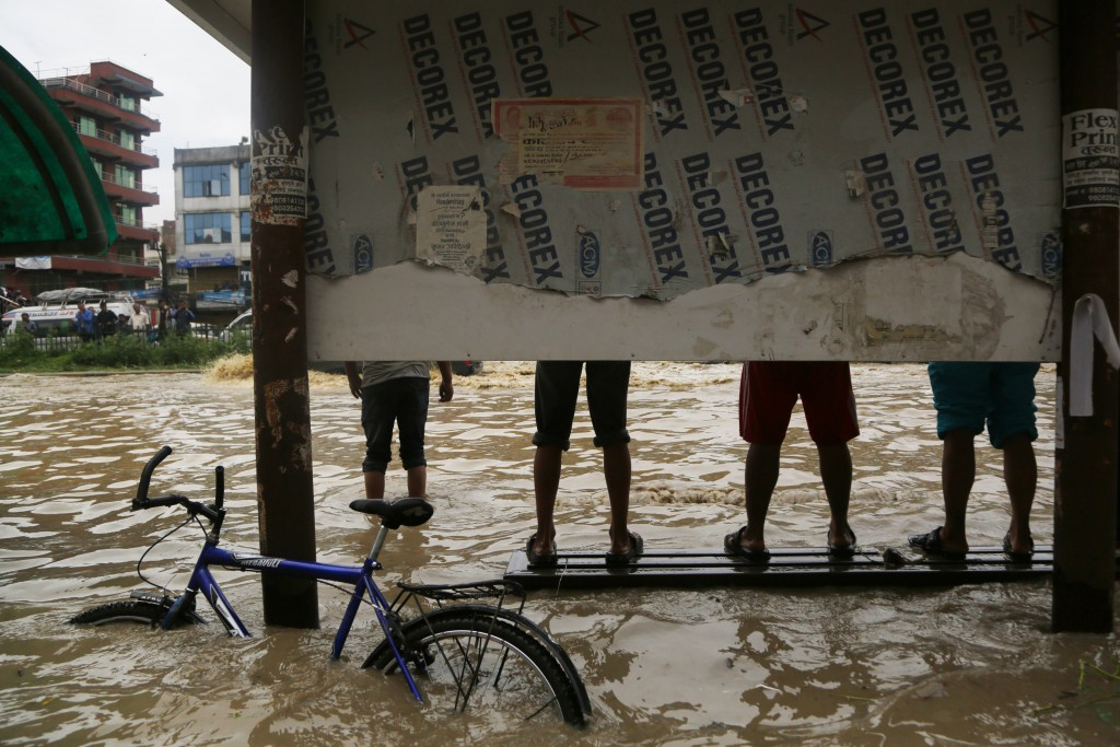 People stand on a bench in a flooded area of Bhaktapur, Nepal, Thursday, July 12, 2018. The flooding was caused by overflowing of the Hanumante River