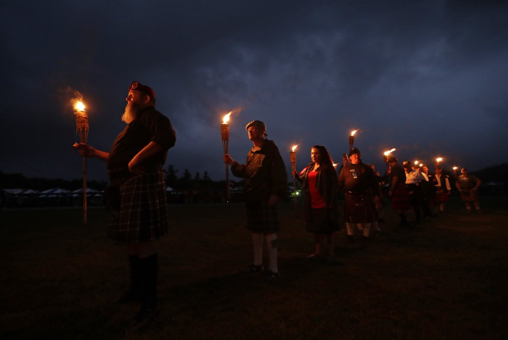 Members of various Scottish clans stand with torches as they prepare to announce their arrival during the opening ceremony for the 63rd Annual Grandfa
