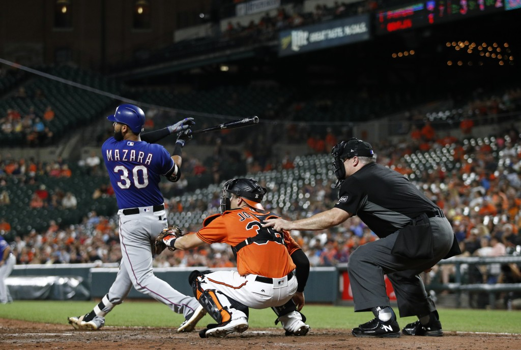 Texas Rangers' Nomar Mazara, left, doubles in front of Baltimore Orioles catcher Caleb Joseph and umpire Bill Welke in the seventh inning of a basebal