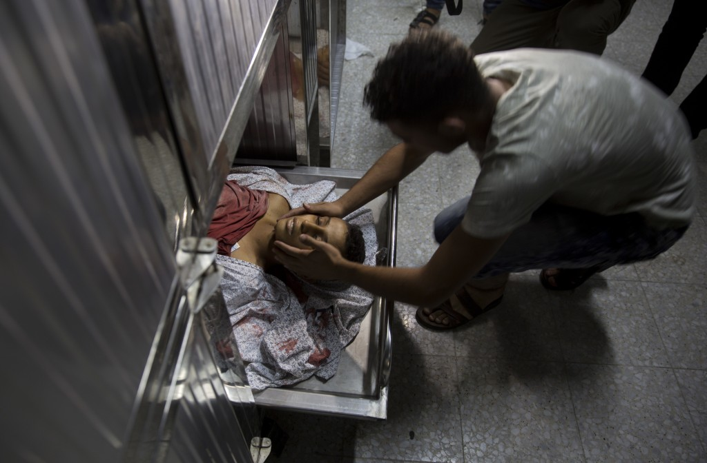 A man mourns over the body of 15-year-old Othman Hellis at the morgue of the Shifa hospital in Gaza City, Friday, July 13, 2018. Gaza's Health Ministr