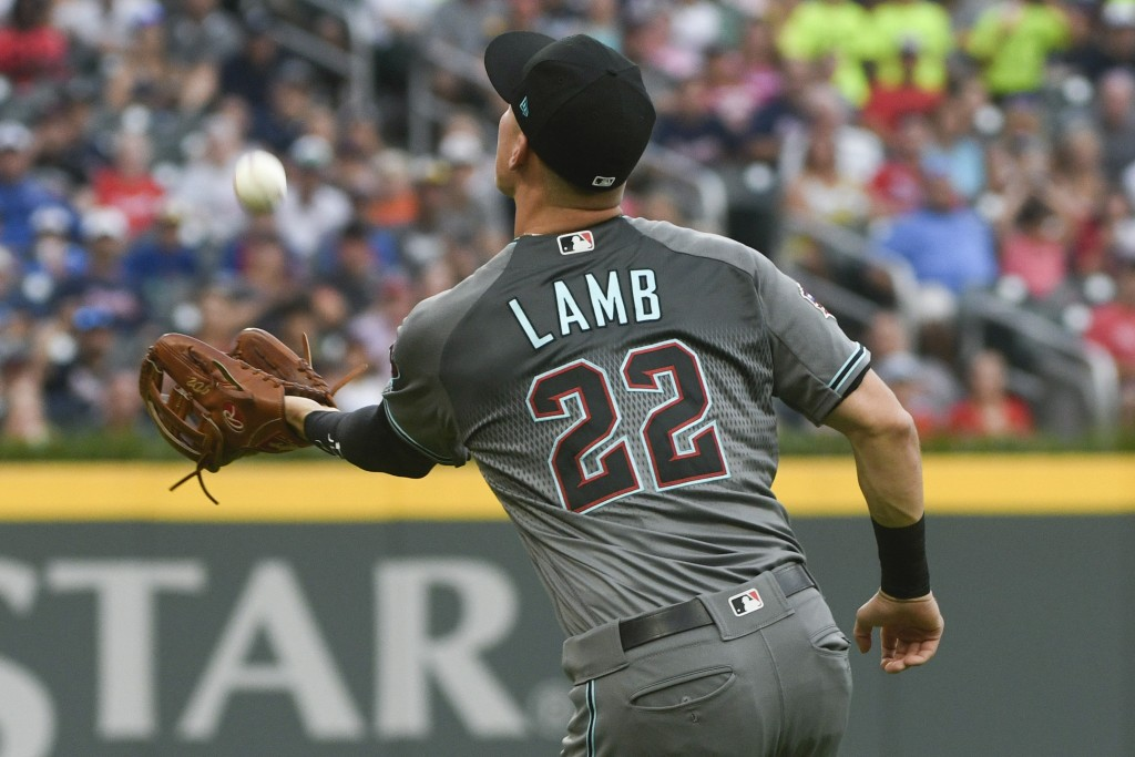 Arizona Diamondbacks third baseman Jake Lamb catches a fly ball to left field hit by Atlanta Braves' Ozzie Albies during the first inning of a basebal