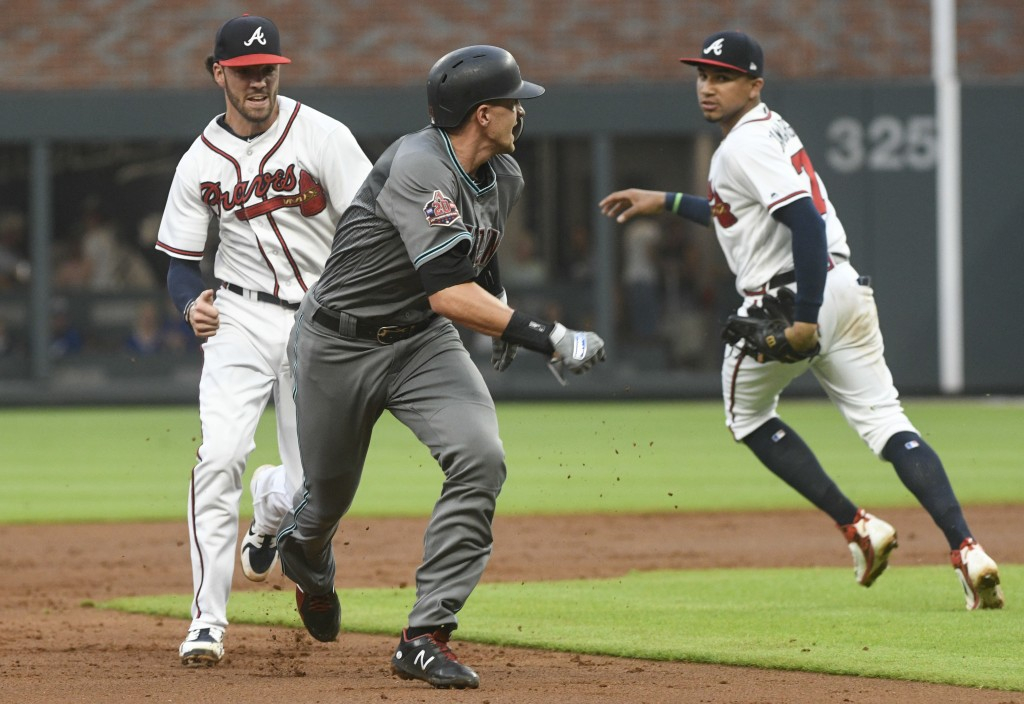 Arizona Diamondbacks' Nick Ahmed, front left, is chased in a rundown by Atlanta Braves shortstop Dansby Swanson, back left, who tags him out with thir