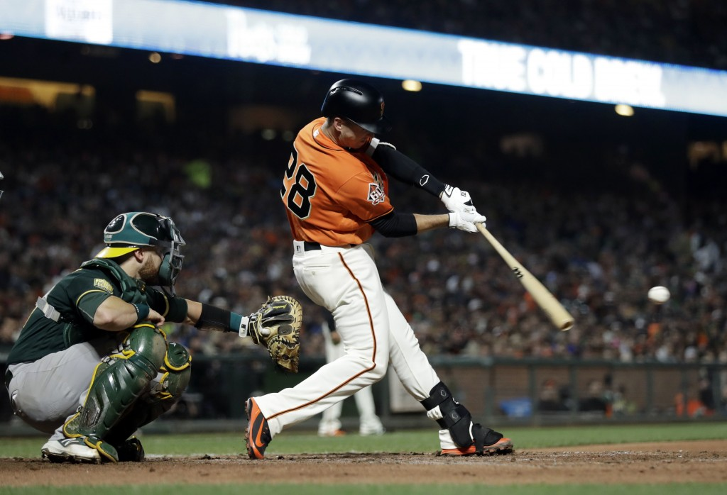 San Francisco Giants' Buster Posey drives in a run with a single during the sixth inning against the Oakland Athletics in a baseball game Friday, July