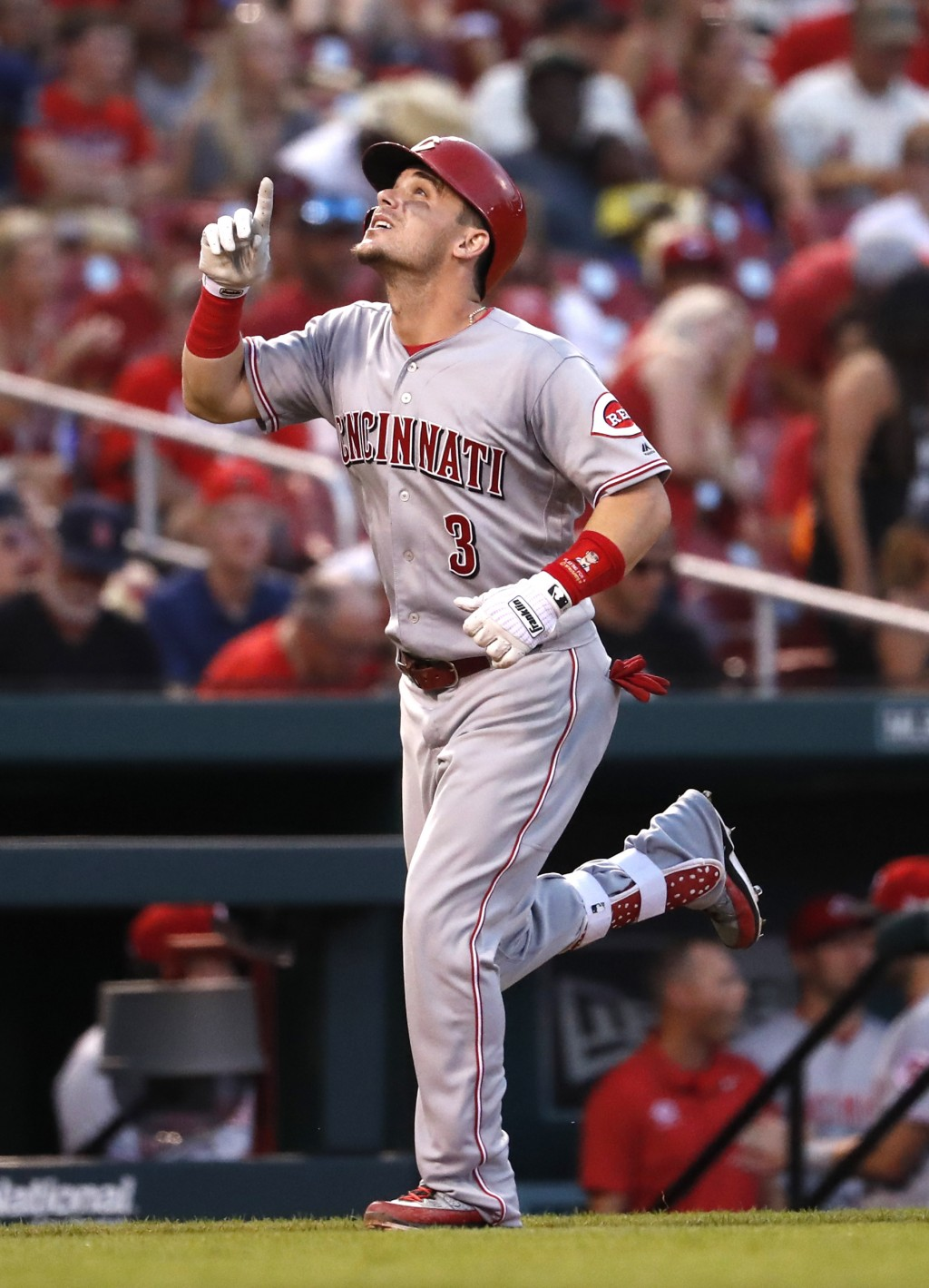 Cincinnati Reds' Scooter Gennett points skyward as he rounds the bases after hitting a solo home run during the third inning of a baseball game agains