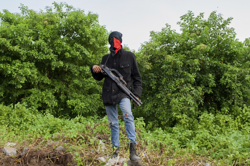 An armed Sandinista paramilitary takes a position before the arrival of President Daniel Ortega, in Masaya, Nicaragua, Friday, July 13, 2018. Accordin