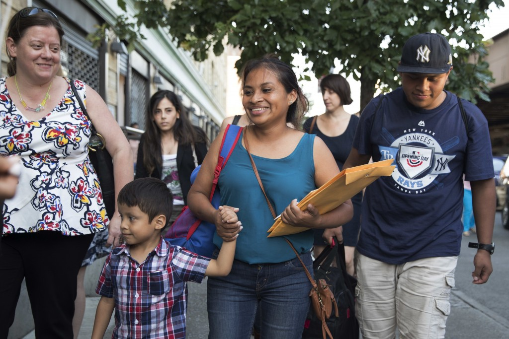 Julie Schwietert-Collazo, left, of Immigrant Families Together, walks with Rosayra Pablo Cruz, center, as she leaves the Cayuga Center with her sons 5