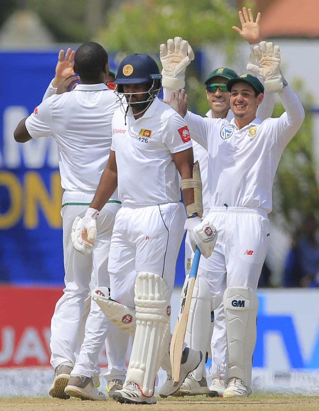 Sri Lanka's Dilruwan Perera, second left, leaves the field as South African players celebrate his dismissal during the third day's play of their first