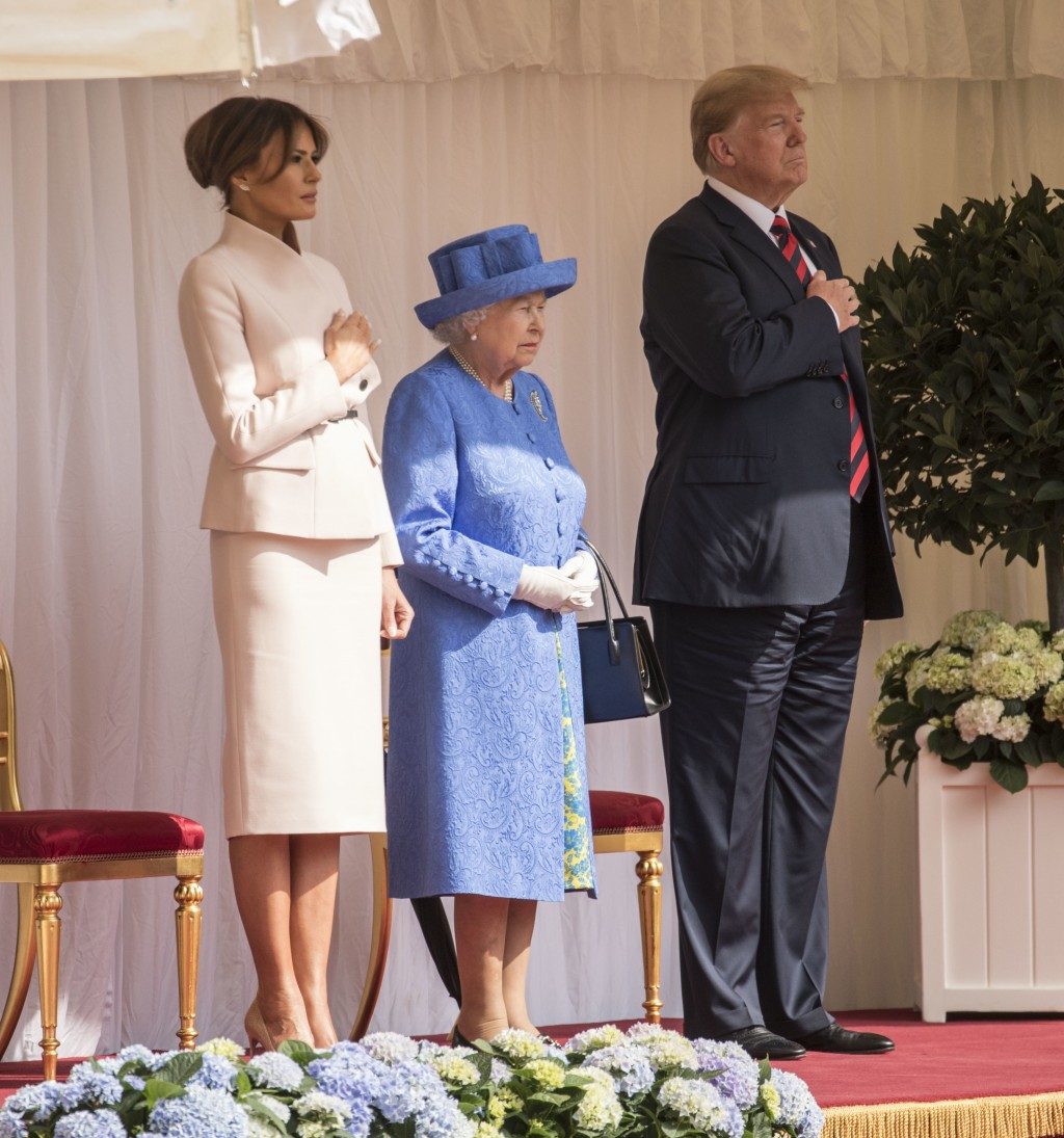 Britain's Queen Elizabeth II, centre stands with US President Donald Trump and first lady Melania on the dias in the Quadrangle as they listen to the