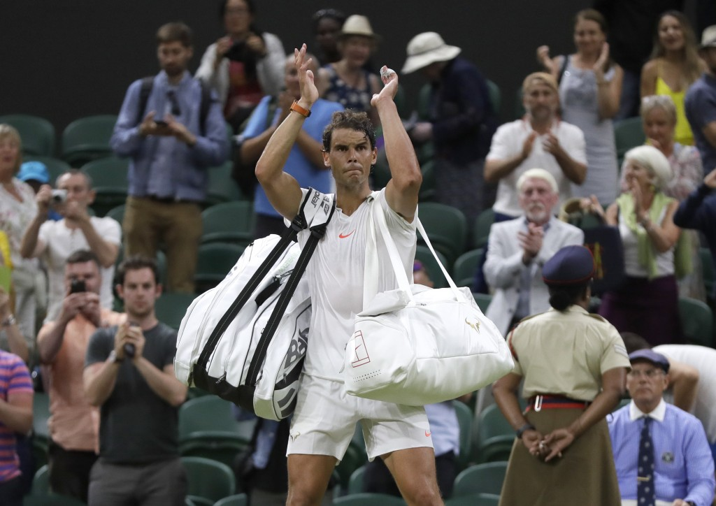 Rafael Nadal of Spain leaves the court after play was suspended in his men's singles semifinals match against Serbia's Novak Djokovic at the Wimbledon