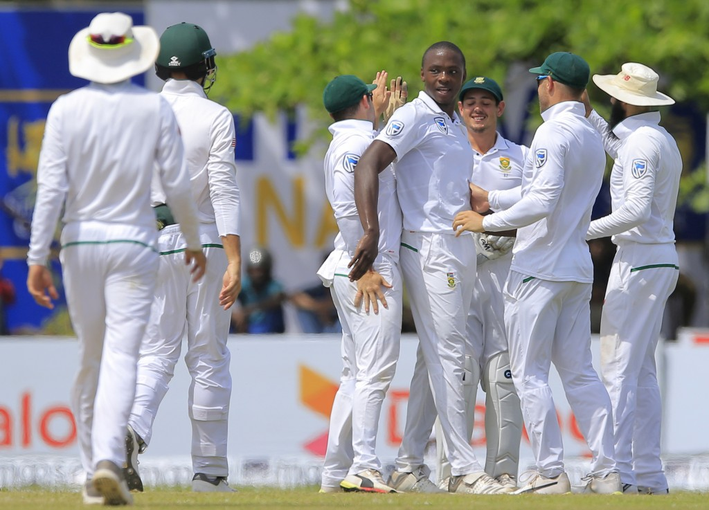 South Africa's Kagiso Rabada, center without cap, is congratulated by his teammates after dismissing Sri Lanka's Niroshan Dickwella during the third d