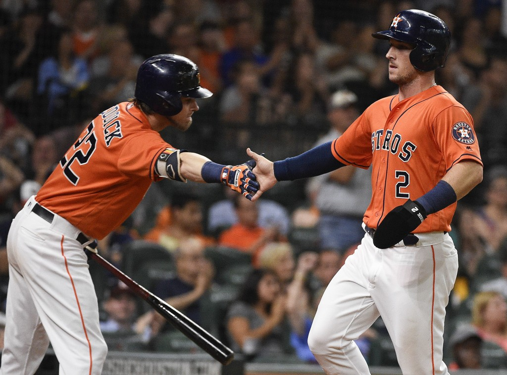 Houston Astros' Alex Bregman, right, shakes hands with Josh Reddick after scoring a run on Yuli Gurriel's RBI-single during the third inning of a base